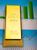 Gold bars with a linear graph, ambient financial concept Stock Photos