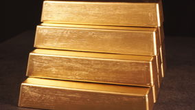 Gold bars. Pyramid from bullions. A stack of gold bars on a dark background stock video footage