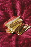 Gold bars on red velvet Stock Image