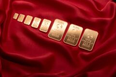 Gold bars on red velvet Stock Images