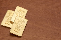 Gold Bars on Wood Surface. One ounce gold bars on dark wood surface Royalty Free Stock Images