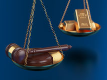 Gold bars with wooden gavel on the scales Royalty Free Stock Images