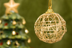 Gold bauble and christmas tree Royalty Free Stock Photo
