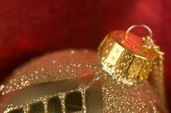 Gold bauble with red backdrop Stock Images