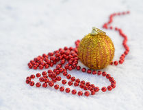 Gold bauble in a snow Stock Photos