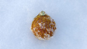 Gold bauble in a snow Stock Images