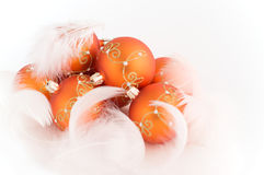 The gold baubles with feathers. Isolated on white background Stock Photos