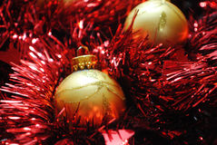 Gold baubles nesting in red tinsel. Gold Christmas baubles nesting in red tinsel Stock Photography