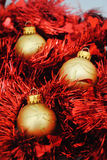 Gold baubles nesting in red tinsel (2). Gold Christmas baubles nesting in red tinsel Stock Photo