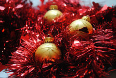Gold baubles nesting in red tinsel (4). Gold Christmas baubles nesting in red tinsel Royalty Free Stock Photo