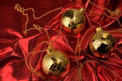 Gold baubles with red backdrop Royalty Free Stock Image