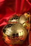 Gold baubles with red backdrop Royalty Free Stock Photos