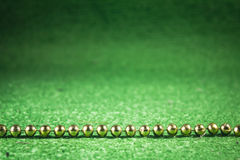 Gold beads on green. Royalty Free Stock Photo