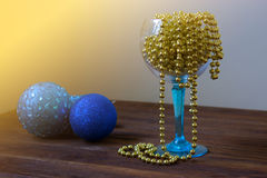 Gold beads in a wineglass. new Year decoration. Christmas orname. New Year decoration. Christmas ornaments, christmas decoration. Christmas holiday decoration Royalty Free Stock Photo