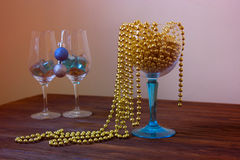 Gold beads in a wineglass. new Year decoration. Christmas orname. New Year decoration. Christmas ornaments, christmas decoration. Christmas holiday decoration Stock Photography