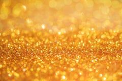 Gold- beleuchtet helle bokeh Beschaffenheit oder Funkeln festliches Gold-backgrou lizenzfreie stockfotos