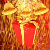 Gold bell and red gift box with golden ribbon Royalty Free Stock Images