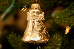 Gold bell shaped Christmas ornament. With all around detail; blurred background Royalty Free Stock Photos