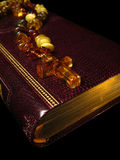 Gold bible. Macro photo of the bible with a gold sawn-off shotgun and an amber necklace with a cross Royalty Free Stock Images