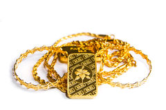 Gold biscuit bar, chains, ornaments on a white background. stock image