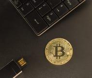 Gold-bitcoin auf dem Tisch nahe bei dem Tastatur- und USB-Blitz-Antrieb Stockfotos