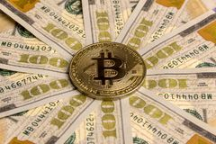Gold bitcoin on the background of hundred-dollar bills, spread out in a circle. The concept of high-value crypto currency, the exc Royalty Free Stock Images