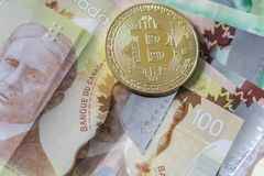 Gold Bitcoin on Canadian Cash. A gold Bitcoin token on Cash stock image
