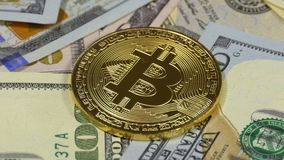 Gold Bitcoin Coin, BTC and Bills of Dollars are Rotating. Crypto Currency Close-up. Dollar banknotes of various denominations on which lies the cryptocurrency stock video footage