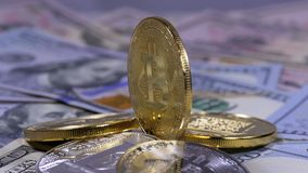 Gold Bitcoin Coin, BTC and Bills of Dollars are Rotating. Different Crypto Currency Close-up. Macro. Dollar banknotes of various denominations on which lies stock video footage