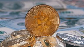 Gold Bitcoin Coin, BTC and Bills of Dollars are Rotating. Different Crypto Currency Close-up. Macro. Dollar banknotes of various denominations on which lies stock footage
