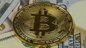 Gold Bitcoin Coin, BTC and Bills of Dollars are Rotating. Crypto Currency Close-up. Dollar banknotes of various denominations on which lies the cryptocurrency stock footage