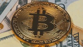 Gold Bitcoin Coin, BTC and Bills of Dollars are Rotating. Crypto Currency Close-up. Dollar banknotes of various denominations on which lies the cryptocurrency stock video