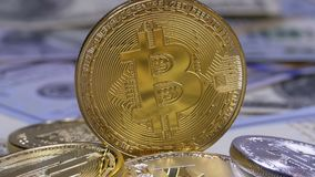 Gold Bitcoin Coin, BTC and Bills of Dollars are Rotating. Different Crypto Currency Close-up. Macro. Dollar banknotes of various denominations on which lies stock video