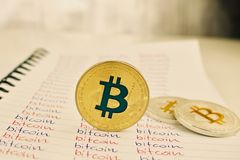 Gold bitcoin coin. Digital currency physical gold and silver bitcoin coins in notebook Stock Image