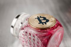 Gold bitcoin coin fragrance concept. Cryptocurrency physical gold bitcoin coin on fragrance pink bottle Royalty Free Stock Images