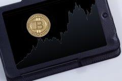 Bitcoin coin chart. Gold Bitcoin coin on tablet Stock Photo