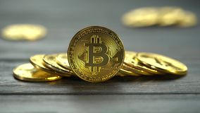 Gold bitcoin coins lie a few handfuls on a dark table with a blurred background. Close up. Gold bitcoin coins lie a few handfuls on a dark table with a blurred stock footage