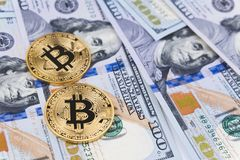 Gold bitcoin coins on one hundred US dollar bills background. Cryptocurrency, New digital currency, Bitcoin exchange to dollar money banknotes and accepted to Stock Image