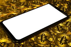 Gold Bitcoin coins pile with smartphone. Gold Bitcoin coins pile with notch white screen smartphone background royalty free stock image
