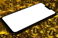 Gold Bitcoin coins pile with smartphone. Gold Bitcoin coins pile with notch white screen smartphone background stock images