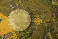 Gold bitcoin concept - computer circuit board with bitcoin processor and microchips. Electronic currency, Internet finance Royalty Free Stock Photos