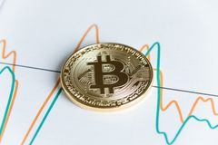 Gold bitcoin cryptocurrency coin on spiking line graph trading c stock photography