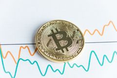 Gold bitcoin cryptocurrency coin on spiking line graph trading c stock image