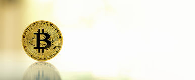 Gold bitcoin cryptocurrency. On reflective table with bright background Royalty Free Stock Photos
