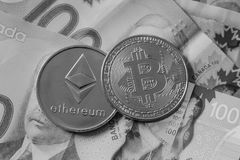 Bitcoin and Etherium Token on Money. A gold Bitcoin and Etherium Token on Canadian Cash royalty free stock photography