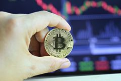 Gold bitcoin in hand of businessman on digital graph background. Gold bitcoin in hand of businessman on digital graph background in concept of cryptocurrency Royalty Free Stock Photos