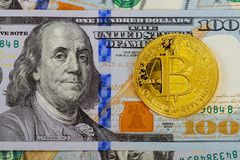 Gold Bitcoin on hundred dollars bills. Close-up, macro shot. The concept of the value of the crypto currency Stock Photo