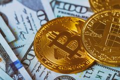 Gold Bitcoin on hundred dollars bills. Bitcoin on us dollar bills electronic money exchange concept. Close-up. Stock Photos