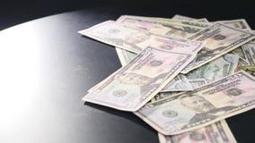 Gold-Bitcoin-Münze auf der Dollar-Banknote, die auf schwarzen Hintergrund sich dreht stock footage