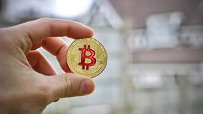 Gold-bitcoin Münze in der Hand stockbilder